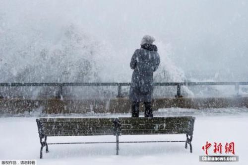 资料图:波士顿郊区市民站在海堤边观看波涛奔涌上岸。