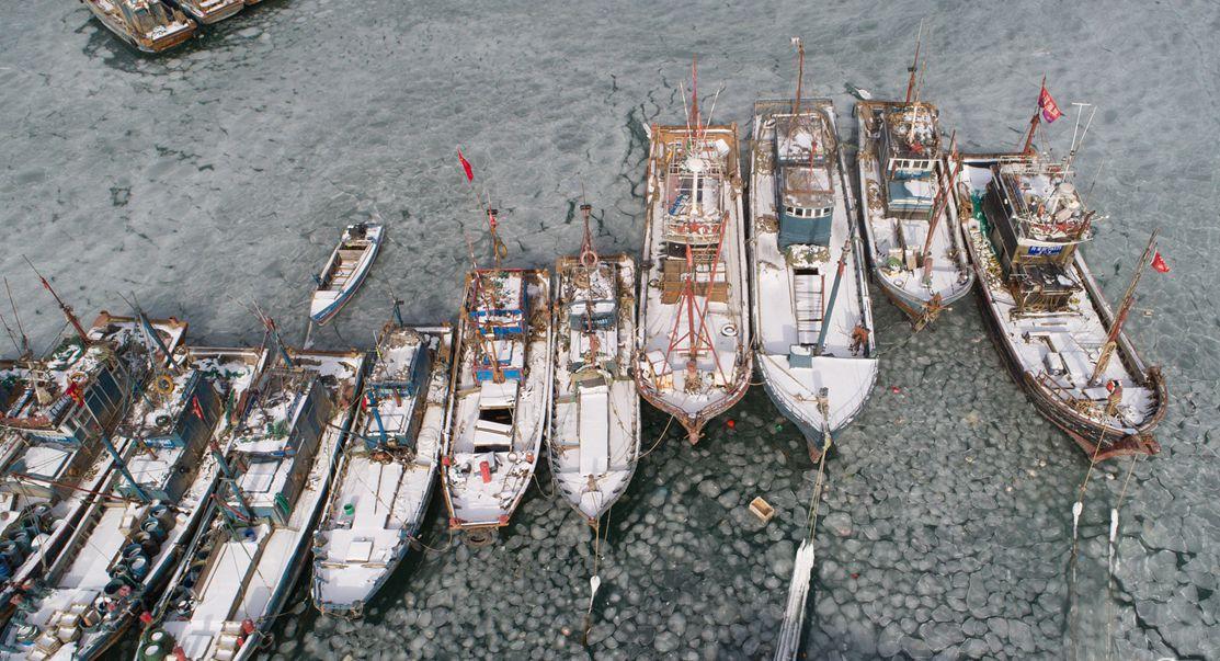 烟台持续低温天气 渔船码头遭海水冰封