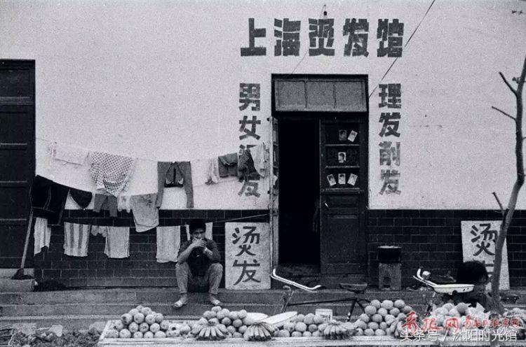 """老照片:图为1982年,一名小商贩在河北路的一家""""上海烫发馆""""门前摆摊卖"""