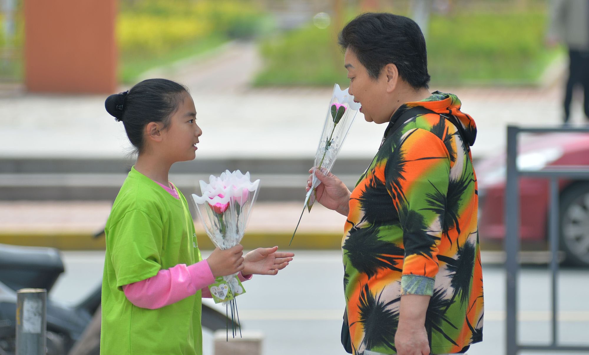 """青岛:小学生制作康乃馨花朵 街头送给""""妈妈们"""""""
