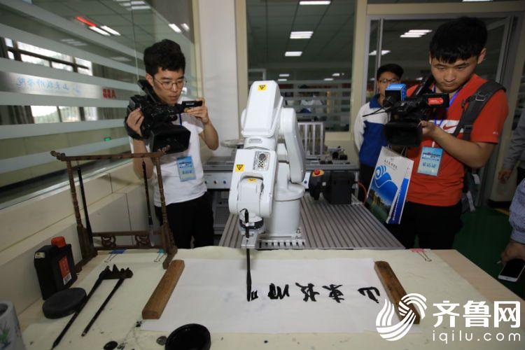 记者参观山东技师学院工业机器人用毛笔写字