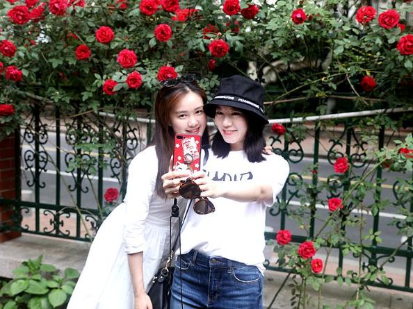 高清:晒初夏大学路林荫之美 女游客排队红墙前打卡