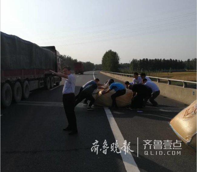 泰安:货物掉落堵占高速公路,众人合力清除