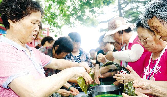 潍坊丹桂里小区60余名居民聚在一起包粽子迎端午