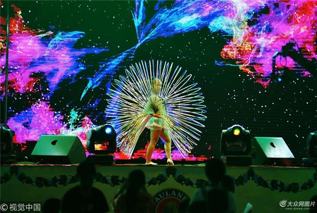 2018年7月22日,青岛,一名演员在青岛啤酒节上用50个呼啦圈进行表演.