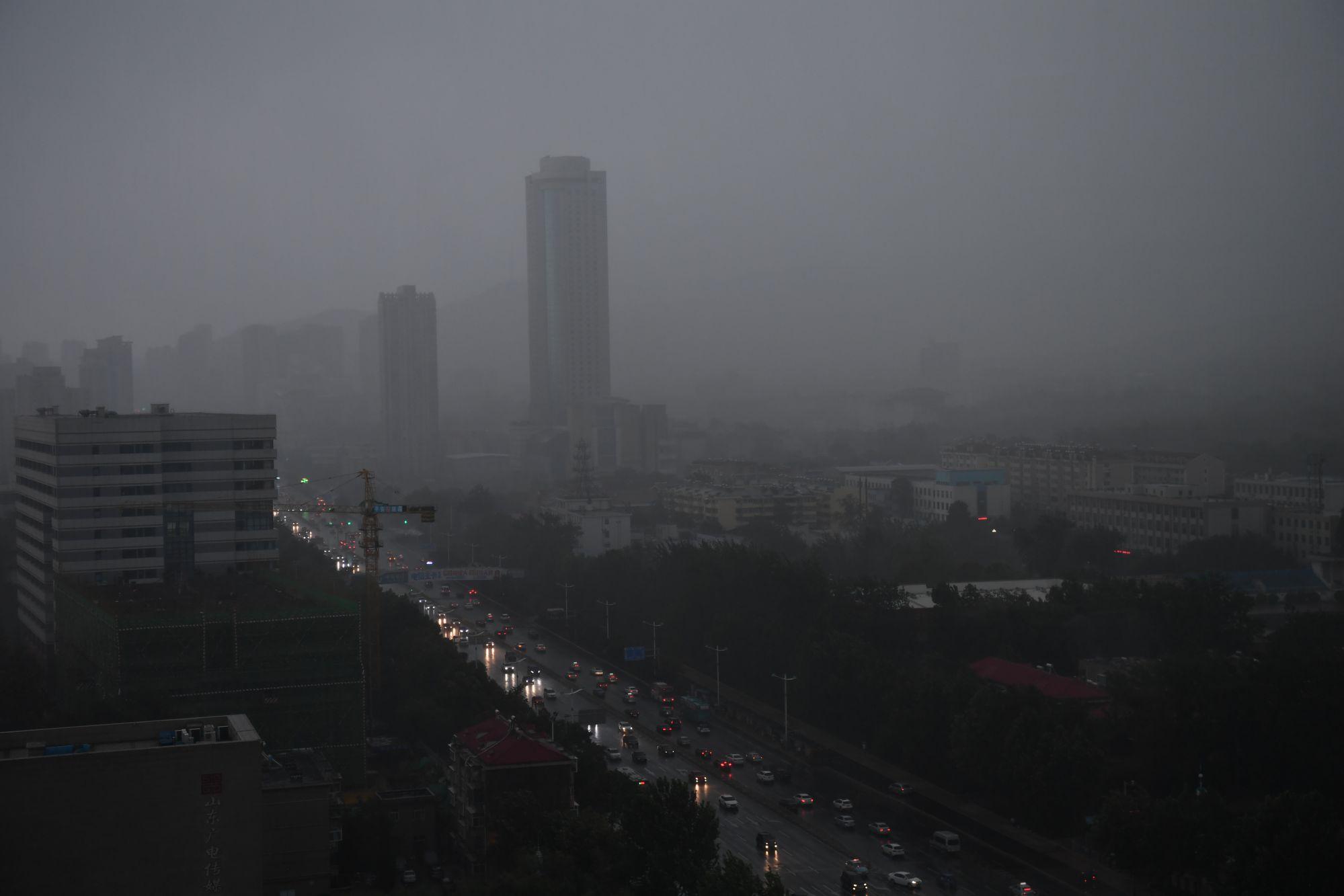 济南午后黑云压城犹如傍晚 市民暴雨中困难出行