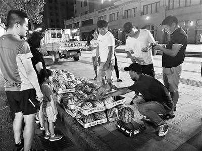 #李恩慧(右一)每天晚上7点准时出摊卖西瓜(资料图)