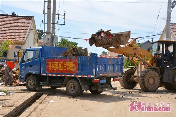 潍坊各地环卫支援寿光 帮村民清理灾后垃圾