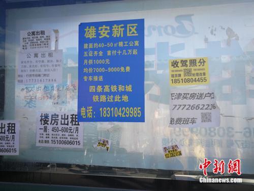 街道公交站牌旁边的综合宣传栏里贴着雄安新区的广告。<a target='_blank' href='http://www.chinanews.com/' >中新网</a>记者 邱宇 摄