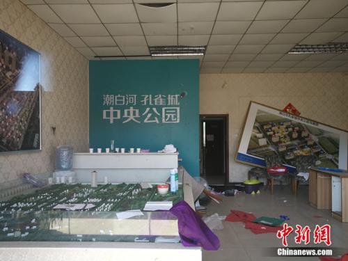 从一家已经关门的售楼处门外望进去,地上散落着废纸、条幅,沙盘上放着落灰的杀虫剂。<a target='_blank' href='http://www.chinanews.com/' >中新网</a>记者 邱宇 摄