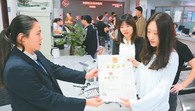 河北省承德市网络代购经营者陈晨(右)从工作人员手中接过带有统一社会信用代码的营业执照。 刘环宇摄(人民图片)