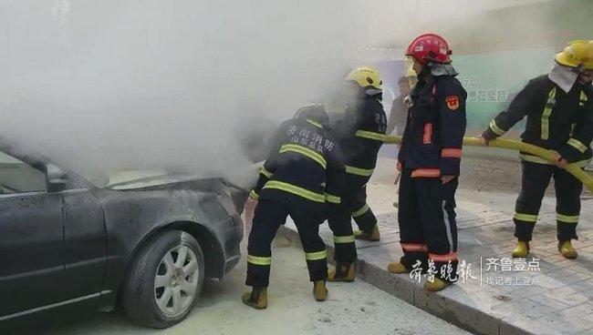 济南街头一黑色轿车突然起火,消防员出动灭火降温