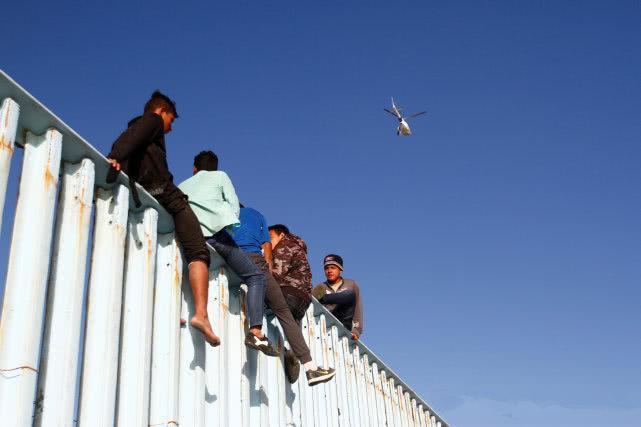 """""""特朗普,我们来了!""""第一批""""大篷车移民""""抵达美墨边境,骑上边境墙"""
