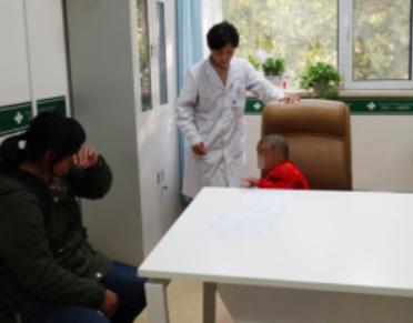 在济南六一儿童医院诊室尹女士与主治医生许玲说其孩子病情忍不住哭泣