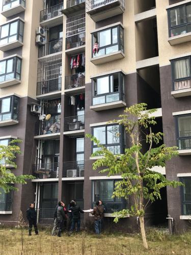 小孩坐4楼窗户上两脚悬空 保安业主拉床单施救