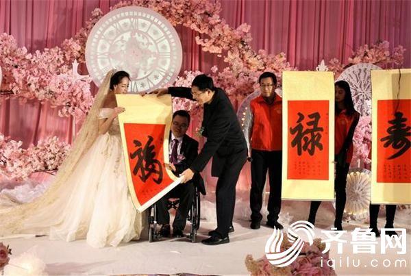 """在新婚典礼上,威海长城爱心大本营发起者刘长城(左3)作为证婚人为新人送上""""福禄寿喜""""作为新婚祝福。"""