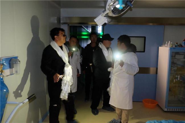 因当地经常停电,烟台毓璜顶医院援藏代表团一行打着手电现场了解当地医院手术室情况