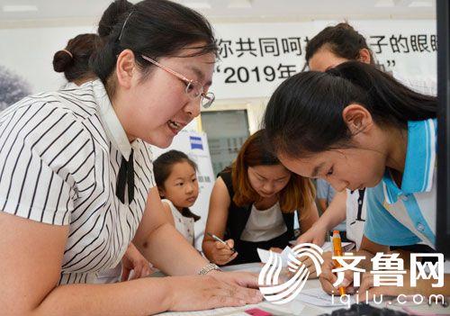滨州姜玉坤眼视光中心工作人员在指导学生填写信息。1