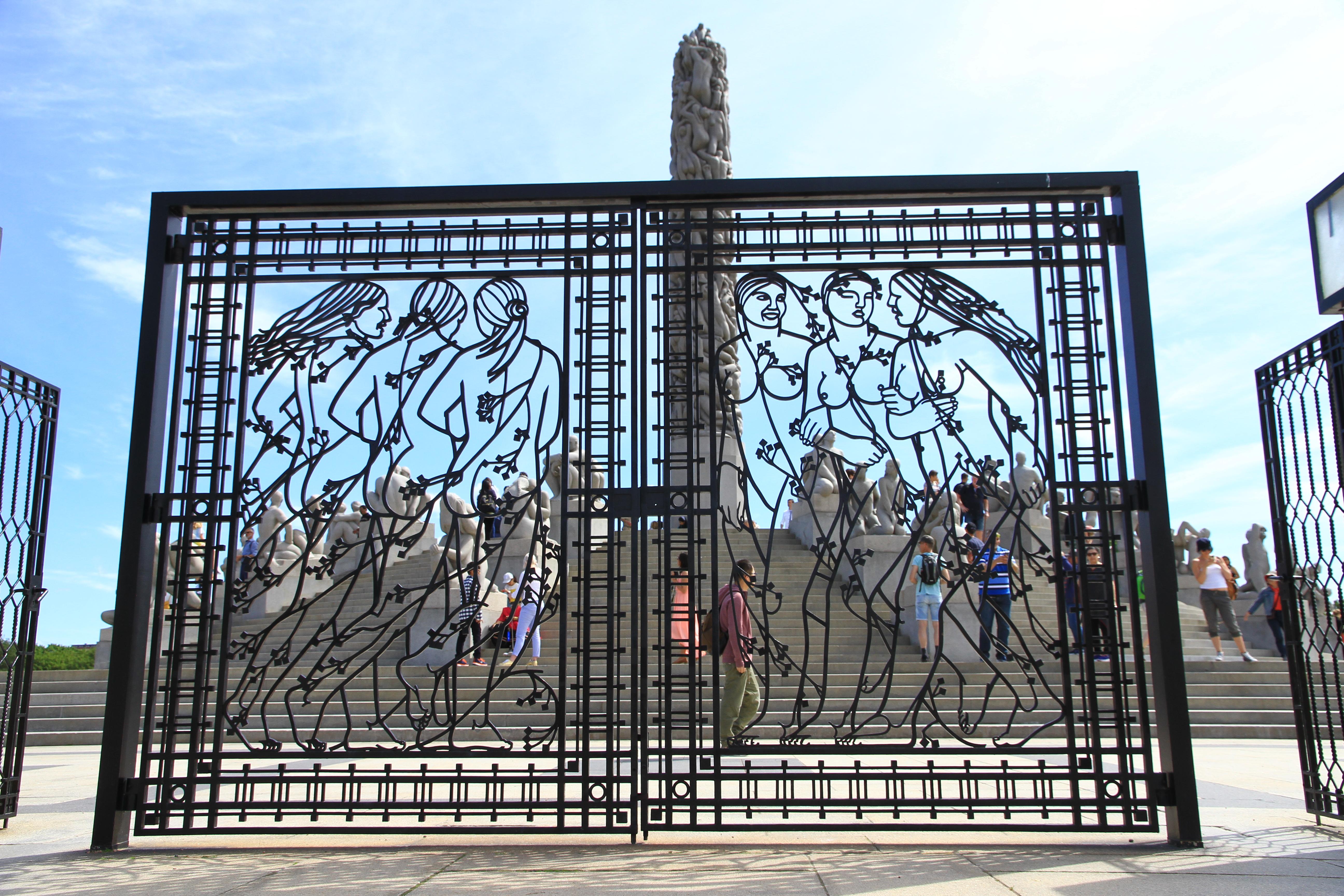"""103、挪威奥斯陆:维格兰雕塑公园:镂空铁门后面是雕塑""""生命之柱""""。该雕塑重达270吨,由121个情态不同、首尾相接、奋力抗争的裸体浮雕造像组成"""
