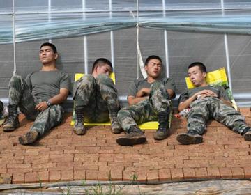 组图 烈日为被红砖作床 救援官兵顶着烈日背靠大棚休整