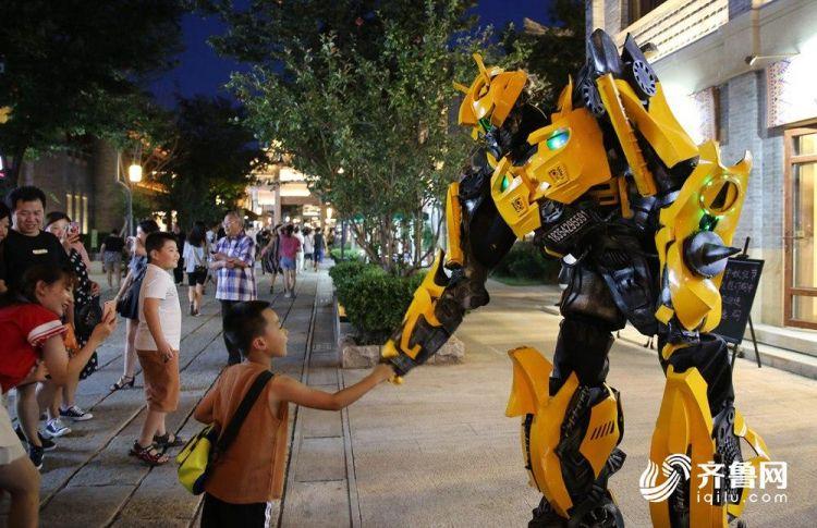 8月17日,在即墨古城内,一名小朋友与人扮机器人互动。(张进刚  摄)电话  13854260100.JPG