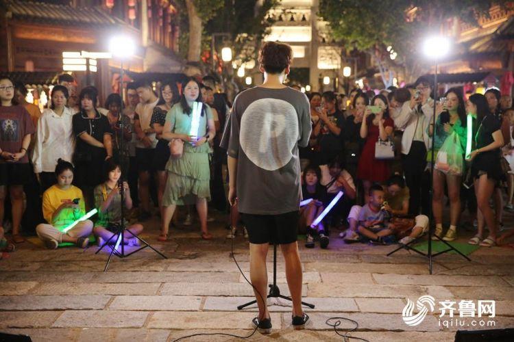 8月17日,当地一名叫周赫的音乐爱好者在古城的一角为市民演出。((张进刚  摄1)电话  13854260100).JPG