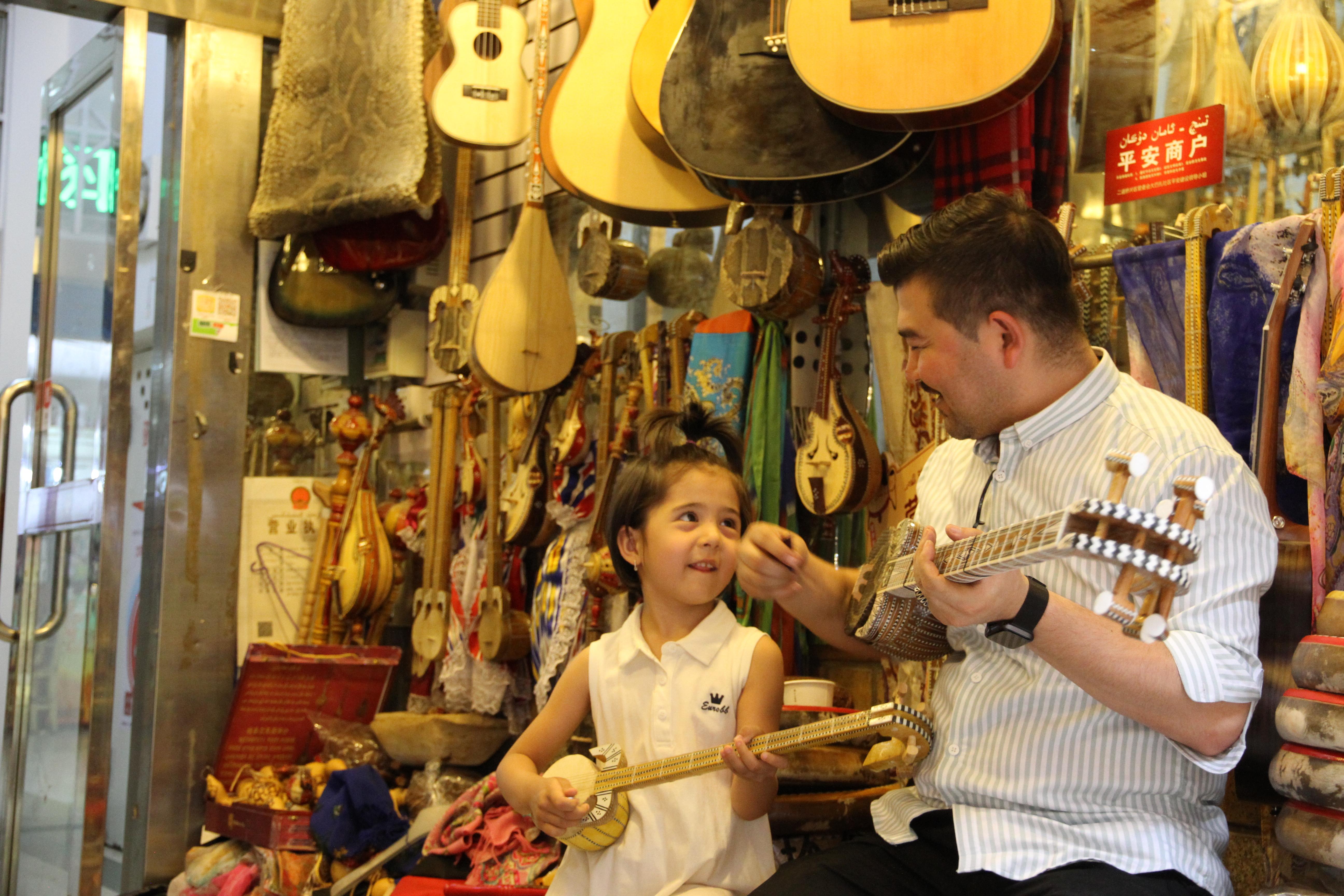 82、乌市国际大巴扎。乐器店自娱自乐的店老板和他的女儿