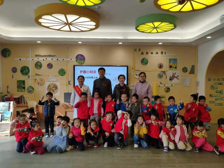 """青年志愿者与幼儿园师生合影 自2018年11月,济南市第二人民医院""""近视早防控""""公益项目开展以来,充分发挥了公立眼科医院的特色优势,为30家幼儿园、小学,5759名小朋友进行了近视筛查和建档工作,为公众健康知识的普及和儿童视力健康做出了积极贡献,用实际行动践行了新时代文明实践志愿服务精神。"""