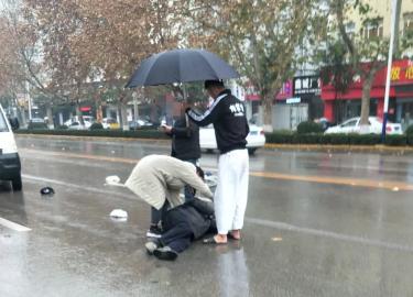 冠县:老人骑车被撞受伤 小伙雨中撑伞陪护