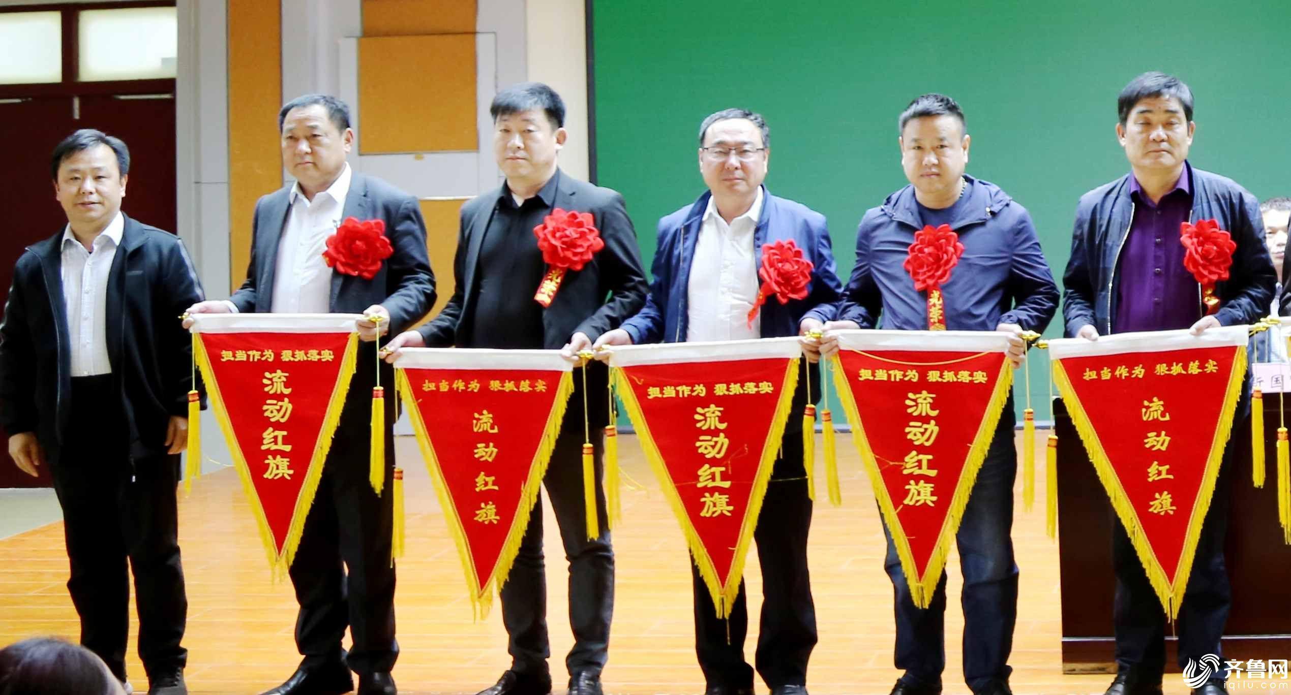 在市东街道组织开展的观摩述职展示评议活动中,毕新军(右一)等党支部书记上台领流动红旗。