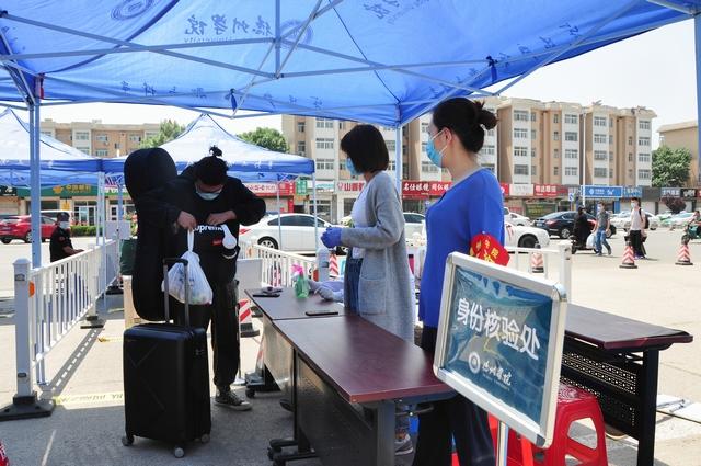 3-5月20日,在德州学院门口,首批省外非毕业年级学生正在排队进行身份核验。