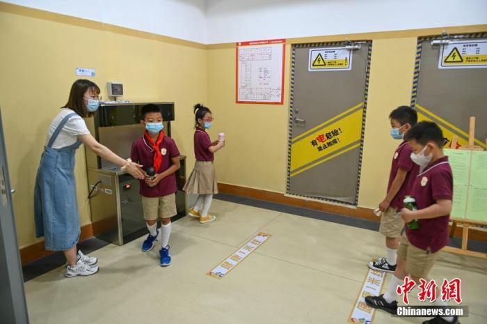 资料图:沈阳市浑南区第十一小学,学生保持一米距离,到饮水机前接水。 于海洋 摄