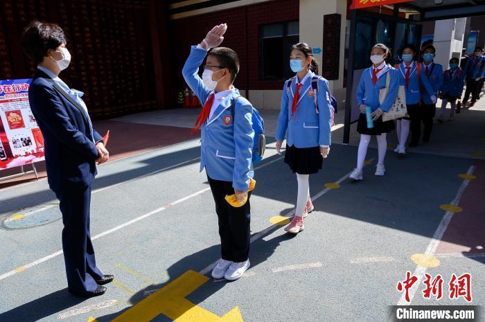 资料图:某小学学生佩戴口罩、间隔排队,次第通过自动测温门,进入校园。韦亮 摄