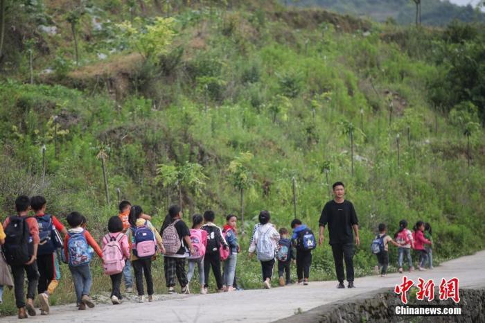 """资料图:彭有兴是贵州省毕节市织金县的一名""""90后""""教师,每个工作日他都会跑步到村口,沿途组织150余名学生排队上下学,每次接送里程8公里。 <a target='_blank' href='http://www.chinanews.com/'>中新社</a>记者 瞿宏伦 摄"""
