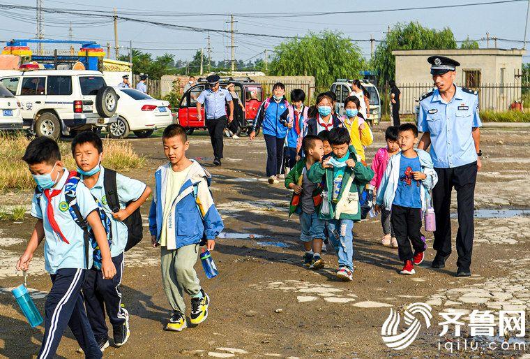 """2020年9月8日,山东省东营市,伏季休渔期结束,秋季捕捞旺季来了。在幼儿园寄宿的学生又多了起来。民警开通""""护学专线"""",护送寄宿的小学生步行上学。 (1)_副本"""